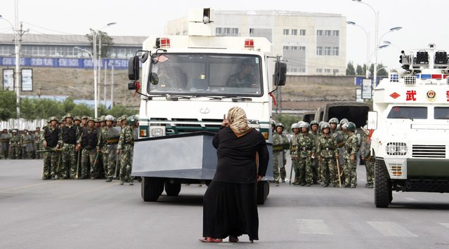 An elderly woman belonging to the Chinese Uyghur Moslem minority  stands defiantly in front of a riot police vehicle and soldiers during a protest in Urumqi, China, 07 July 2009. Authorities said at least 140 people were killed and over 800 injured when Muslim Uighurs rioted in its restive Xinjiang region in some of the deadliest ethnic unrest to have hit the country for decades. (Photo by Oliver Weiken/EPA)