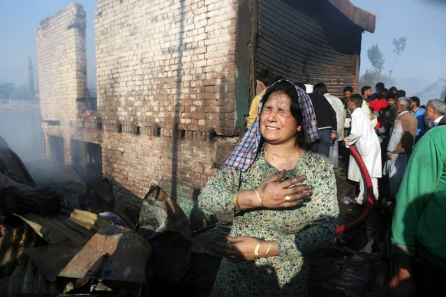 A Kashmiri woman wails in front of her gutted house in Srinagar, summer capital of Indian Kashmir, 29 April 2014. At least 27 shanties, two residential houses and shops were gutted in the fire. No casualties have been reported so far, according to officials. (Photo by Farooq Khan/EPA)