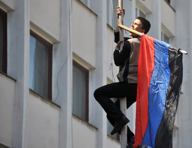 "A pro-Russian activist climbs up on the flagpole as he holds flag of so-called  Donetsk Republic in the teeth after Ukrainian policemen left their guarding outside of state city building in southern Ukrainian city of Mariupol on May 7, 2014. Townhall is back in ""control"" of separatists after national guard stormed in briefly raised Ukrainian flag. They left peacefully this morning. Building still thick with teargas. Building now is mainly empty and ransacked. (Photo by Genya Savilov/AFP Photo)"