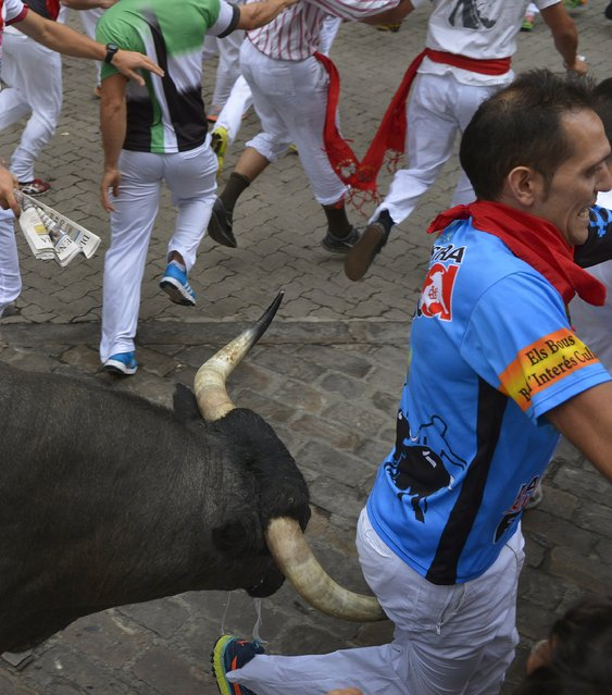 A runner is gored by a Jose Escolar fighting bull at Telefonica corner during the fifth running of the bulls of the San Fermin festival in Pamplona, northern Spain, July 11, 2015. Four runners were gored in the run that lasted two minutes and forty seconds, according to local media. (Photo by Vincent West/Reuters)