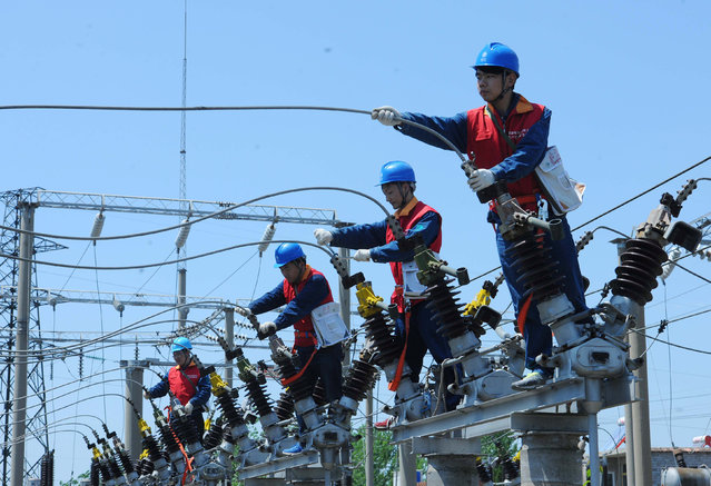 Employees check electricity cables in Chuzhou, Anhui province, China, April 28, 2016. (Photo by Reuters/China Daily)