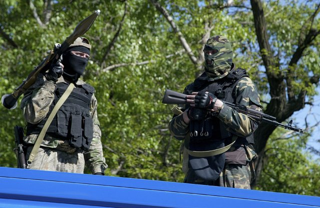 Pro-Russian gunmen hold their weapons as they try to block a military base of Ukrainian riot police in Donetsk, Ukraine, Tuesday, May 6, 2014. The pro-Russian insurgent gunmen surrounded the base and said they were holding negotiations with commanders inside to ensure that they did not join forces with government-allied groups. (Photo by Alexander Ermochenko/AP Photo)