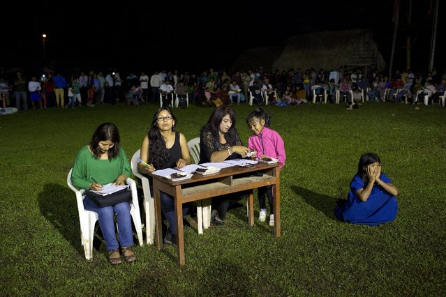 In this June 23, 2015 photo, a panel of invited judges evaluate contestants in the Ashaninka Indian beauty contest, in Otari Nativo, Pichari, Peru. Participants were each asked two varying questions about local geography and politics, such as to identify nearby rivers or to name Peru's president, who is Ollanta Humala. (Photo by Rodrigo Abd/AP Photo)