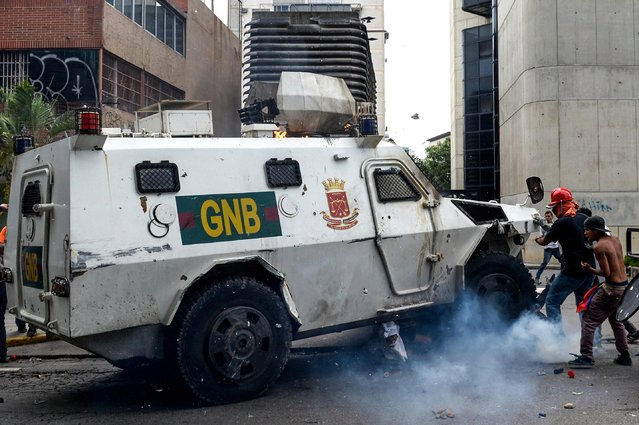 A Venezuelan National Guard riot control vehicle runs over an opposition demonstrator during a protest against Venezuelan President Nicolas Maduro, in Caracas on May 3, 2017. (Photo by Federico Parra/AFP Photo)
