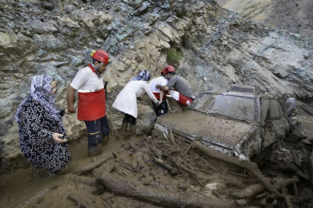 In this photo released by the Hamshahri Photo Agency on Monday, July 20, 2015, Iranian rescue crew members help people walk in a flooded road in Kan district, northern Tehran, Iran. Its state media said heavy rains triggered deadly flash floods in a mountainous area in the country's north. (Photo by Ali Ghanbarlou/Hamshahri Photo Agency via AP Photo)
