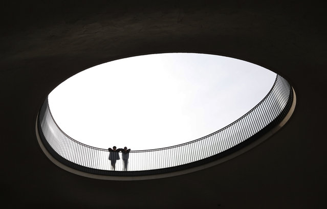 Men look through a hole in front of a building in Tokyo on May 28, 2014. (AP Photo/Shizuo Kambayashi)