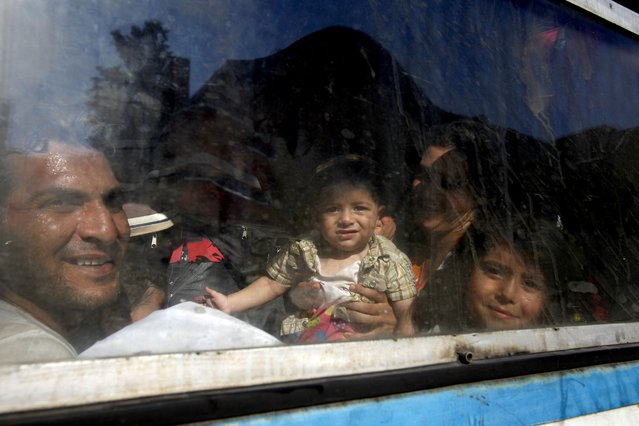 In this photo taken on Thursday, July 23, 2015 migrants look through a window of a train on their way to Serbia at the railway station in the southern Macedonian town of Gevgelija. (Photo by Boris Grdanoski/AP Photo)