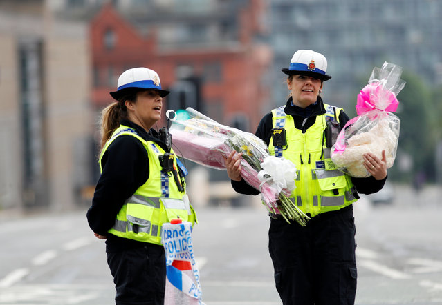 A community support officer carries flowers near Manchester Arena in Manchester, Britain May 24, 2017. (Photo by Peter Nicholls/Reuters)