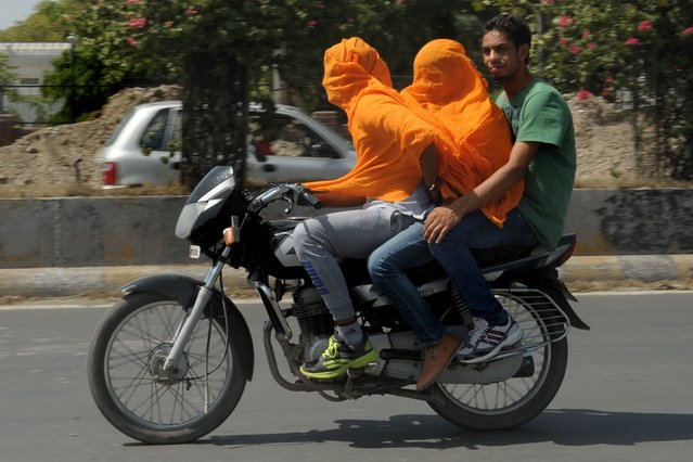 Indian motorcyclists cover their heads as they travel in the heat in Amritsar on June 10, 2014. Amritsar and Ludhiana in Punjab and Hisar and Bhiwani in Haryana have been reeling under severe heat conditions with temperatures hovering between 45-47 degrees celsius. (Photo by Narinder Nanu/AFP Photo)