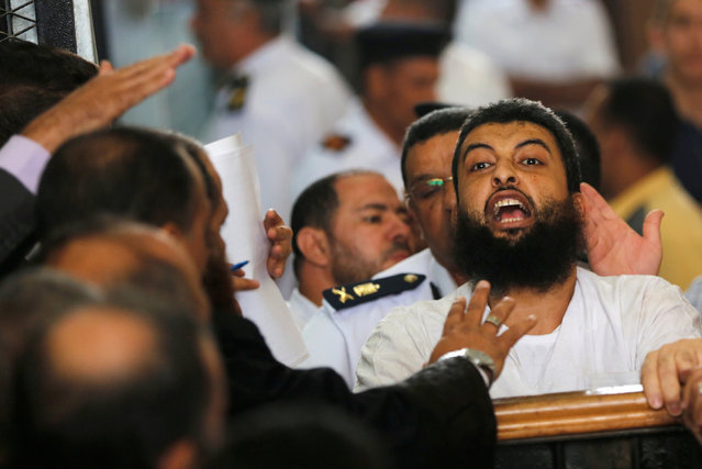 A defendant, who is a member of the Muslim Brotherhood, shouts solgans against the Interior Ministery during the trial of brotherhood members for their armed sit-in at Rabaa square, at a court on the outskirts of Cairo, Egypt May 31, 2016. (Photo by Amr Abdallah Dalsh/Reuters)