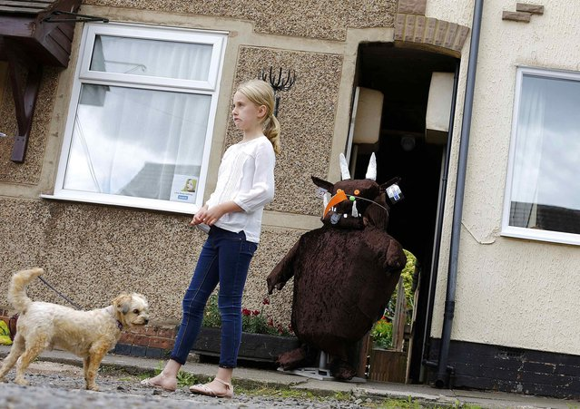 "A girl turns away from a scarecrow of the children's book character ""The Gruffalo"" during the Scarecrow Festival in Heather, Britain July 29, 2015. (Photo by Darren Staples/Reuters)"