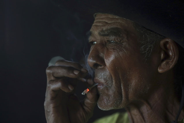 In this May 17, 2017 photo, cowboy Joao Aquino Pereira smokes at dawn on a ranch in Corumba, in the Pantanal wetlands of Mato Grosso do Sul state, Brazil. (Photo by Eraldo Peres/AP Photo)
