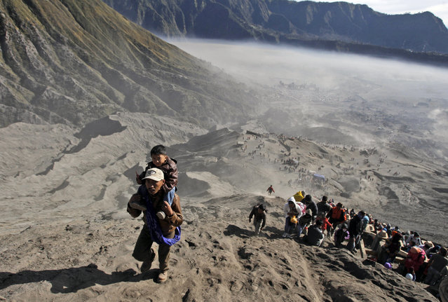 Worshippers climb Mount Bromo to throw offerings into its crater during Yadnya Kasada festival in Probolinggo, East Java, Indonesia, Saturday, August 1, 2015. (Photo by AP Photo/Trisnadi)