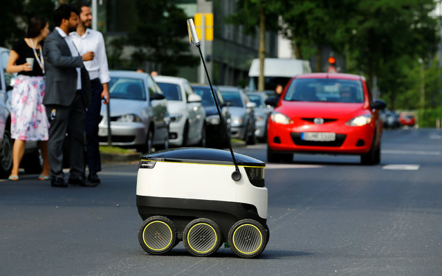 A Starship Technologies commercial delivery robot crosses a street during a live demonstration in front of the headquarters of Metro AG in Duesseldorf, Germany, June 7, 2016. The six-wheel electrical delivery robot, designed by Skype founders Ahti Heinla and Janus Friis, can autonomously navigate and carry a maximum load of 20 kilograms over a distance of six kilometres from its base station at a maximum speed of six km/h. (Photo by Wolfgang Rattay/Reuters)