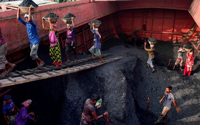 Labourers unload coal from a cargo ship in Gabtoli on the outskirts of Dhaka on November 6, 2019. (Photo by Munir Uz Zaman/AFP Photo)