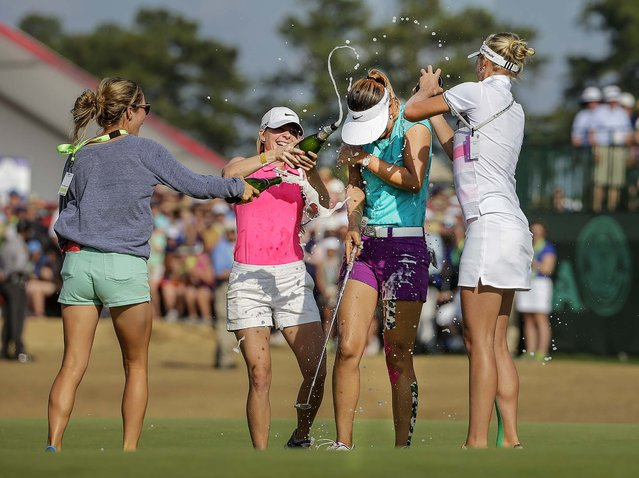 Michelle Wie is doused by friends after winning the U.S. Women's Open golf tournament in Pinehurst, N.C., on June 22, 2014. (Photo by Chuck Burton/Associated Press)