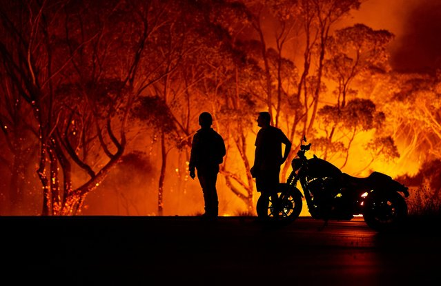 Residents look on as flames burn through bush on January 04, 2020 in Lake Tabourie, Australia. A state of emergency has been declared across NSW with dangerous fire conditions forecast for Saturday, as more than 140 bushfires continue to burn. There have been eight confirmed deaths in NSW since Monday 30 December. 1365 homes have been lost, while 3.6 million hectares have been burnt this fire season. (Photo by Brett Hemmings/Getty Images)
