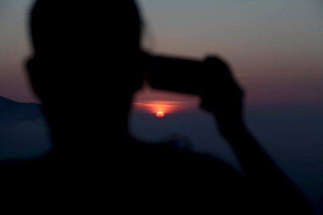 A hiker takes a picture of the sunrise while touring La Huasteca park, on the outskirts of Monterrey, Mexico, July 26, 2015. (Photo by Daniel Becerril/Reuters)