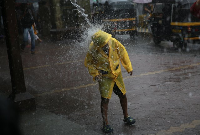 A boy stands beneath water poring from a roof during monsoon rains in Mumbai, India, Monday, July 7, 2014.The monsoon rains usually hit India from June to September. (Photo by Rafiq Maqbool/AP Photo)