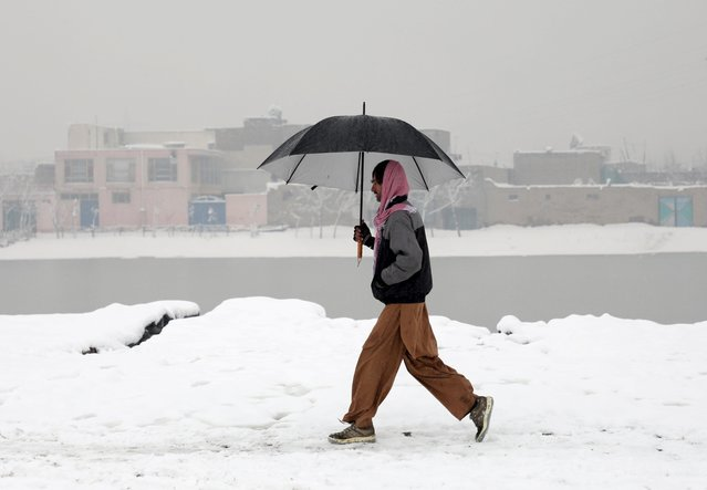 An Afghan man holds an umbrella as he walks during a snowy day in Kabul, Afghanistan on January 2, 2020. (Photo by Omar Sobhani/Reuters)