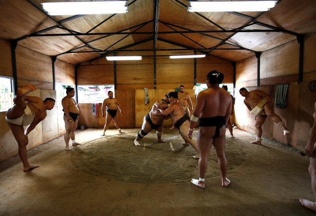 """Mongolian-born Tomozuna Oyakata, or master of the Tomozuna stable (L), attends his wrestlers' training session in Nagoya, Japan on July 18, 2017. The wrestlers, or """"rikishi"""", at the prestigious Tomozuna stable spend more than three hours each morning practising holds in Japan's 15-century-old national sport, with defeat facing the first to fall or be forced out of the ring. (Photo by Issei Kato/Reuters)"""