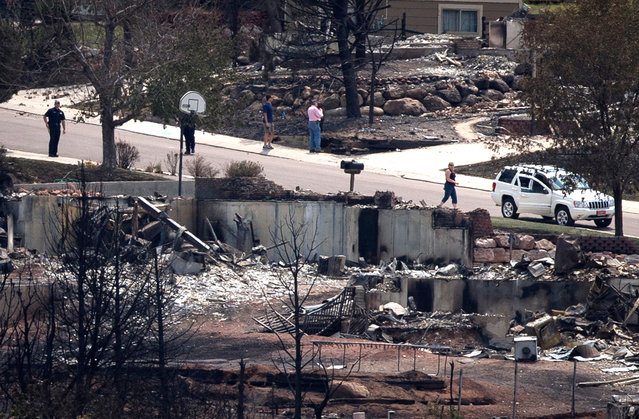 Policemen stand guard near residents who were temporarily allowed to visit their homes destroyed by the Waldo Canyon fire in the Mountain Shadows neighborhood of Colorado Springs, on July 1, 2012. (Reuters/Adrees Latif)
