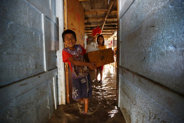A boy carries out belongings recovered from his house after floodwaters caused by heavy rainfall flowing from the swollen Bagmati River entered a slum in Kathmandu, Nepal August 17, 2015. (Photo by Navesh Chitrakar/Reuters)