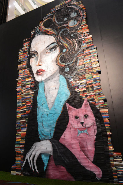 """""""Discarded Romance"""". This is the largest book installation I've done to date.  It was originally shown in Hong Kong Times Square. It's 24 feet high by 13 feet wide.  It now permanently resides at Fully Booked in Manila, Philippines. (Photo and caption by Mike Stilkey)"""