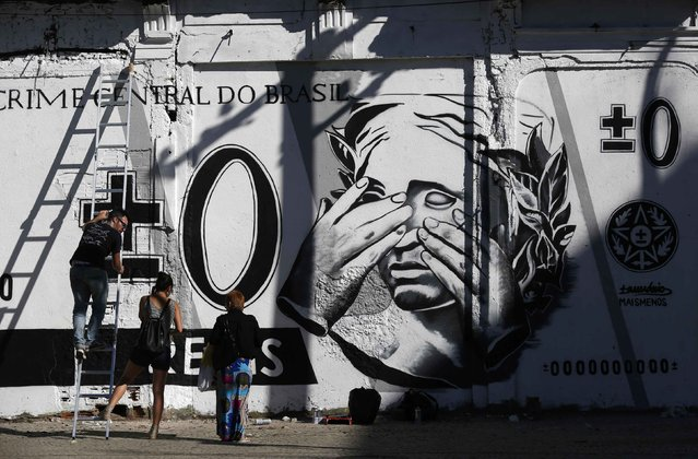 People stand in front of a graffiti mocking the Brazilian currency note, the real, in downtown Rio de Janeiro July 31, 2014. (Photo by Pilar Olivares/Reuters)