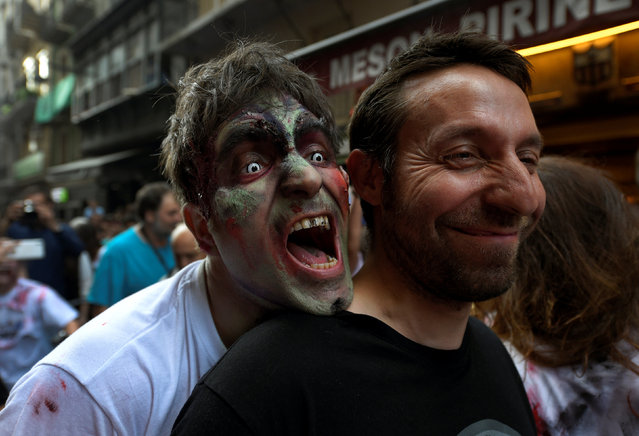 A reveller dressed as a zombie bites another reveller during an enactment of the running of the bulls a day before the start of the San Fermin festival in Pamplona, northern Spain, July 5, 2016. (Photo by Eloy Alonso/Reuters)