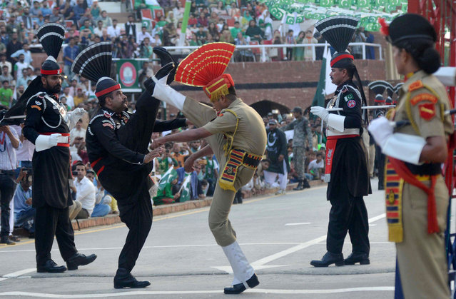 Pakistani Rangers (black) and Indian Border Security Force personnel (brown) perform perform during the daily beating of the retreat ceremony at the India- Pakistan Wagah Border Post, some 35 kms west of Amritsar on August 14, 2017. Pakistan celebrates its independence on August 14, one day before India' s independence day on August 15. (Photo by Narinder Nanu/AFP Photo)