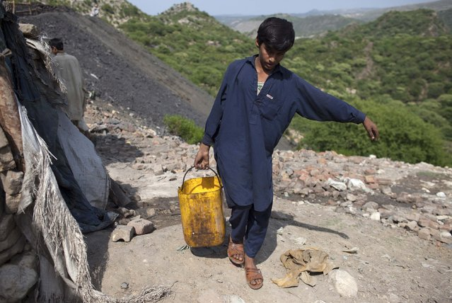 Samiullah, who says he is 14-years-old, carries water for his uncle's bath at a coal field in Choa Saidan Shah, Punjab province, May 5, 2014. (Photo by Sara Farid/Reuters)