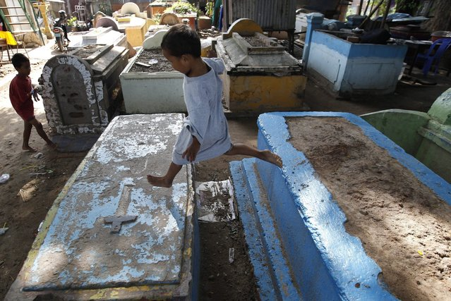 A picture made available on 06 July 2016 shows a young Cambodian boy jumping from tomb to tomb at his home, in the Doeum Sleng cemetery, a Chinese – Vietnamese cemetery that is now home to at least 95 poor families, on the outskirts of Phnom Penh, Cambodia, 02 July 2016. The cemetery village houses families who cook, sleep, wash and play amidst the tombstones containing the departed. (Photo by Mak Remissa/EPA)