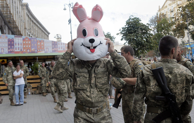 A soldier tries a cartoons character's costume on during a rehearsal for the Independence Day military parade in the center of Kiev, Ukraine, Saturday, August 22, 2015. (Photo by Efrem Lukatsky/AP Photo)