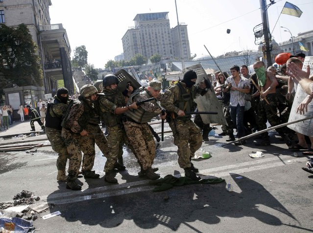 Pro-government forces (L) clash with protesters at Independence Square in Kiev August 7, 2014. (Photo by Konstantin Chernichkin/Reuters)