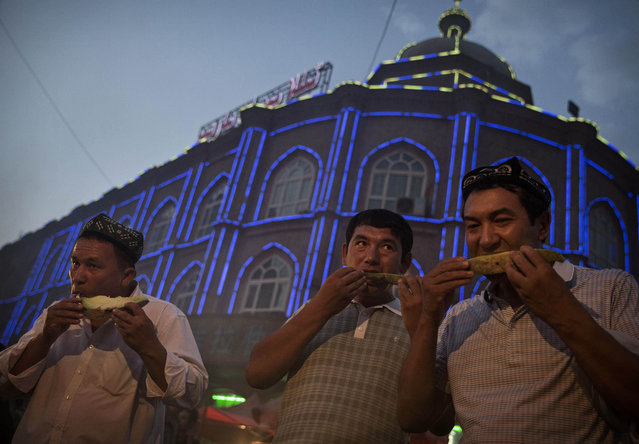 Uyghur men eat watermelon as they break their Ramadan fast before the Eid holiday at a night market on July 28, 2014 in old Kashgar, Xinjiang Province, China. (Photo by Kevin Frayer/Getty Images)