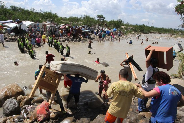 People carry their household belongings across the Tachira River from Venezuela, foreground, to Colombia, near San Antonio del Tachira, Venezuela, Tuesday, August 25, 2015, during a mass exodus of Colombians living on the Venezuelan side of the border. (Photo by Eliecer Mantilla/AP Photo)
