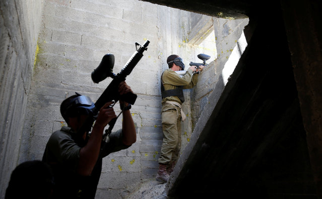 Israeli soldiers from the Nahal Infantry Brigade use paintball guns during an urban warfare training in the West Bank Jewish settlement of Alei Zahav, near Ariel July 13, 2016. (Photo by Baz Ratner/Reuters)