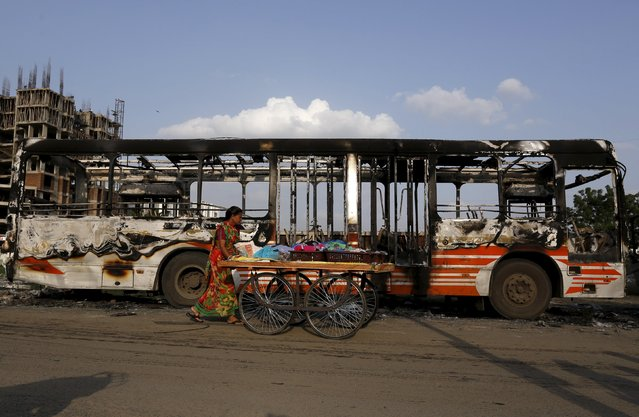 A woman pushes a cart past a damaged passenger bus which was burnt in Wednesday's clashes between protesters and police in Ahmedabad, India, August 27, 2015. (Photo by Amit Dave/Reuters)
