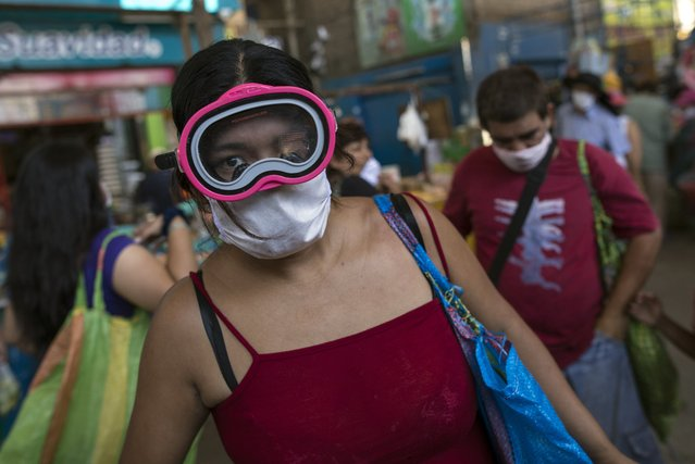 A woman wears a scuba mask and a surgical mask as a precaution against the spread of the new coronavirus, while buying food in a popular market in Lima, Peru, Monday, March 23, 2020. The vast majority of people recover from the COVID-19 disease. (Photo by Rodrigo Abd/AP Photo)