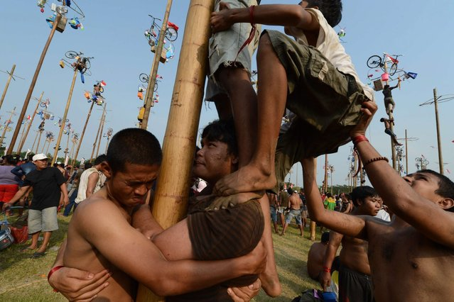 "Indonesians participate in a local competition called ""panjat pinang"" in which people try to climb greased poles that have prizes and flags attached to the top, during an event to celebrate Indonesia's Independence Day in Jakarta on August 17, 2014. Indonesia marked the 69th anniversary of its independence from Dutch rule on August 17. (Photo by Romeo Gacad/AFP Photo)"