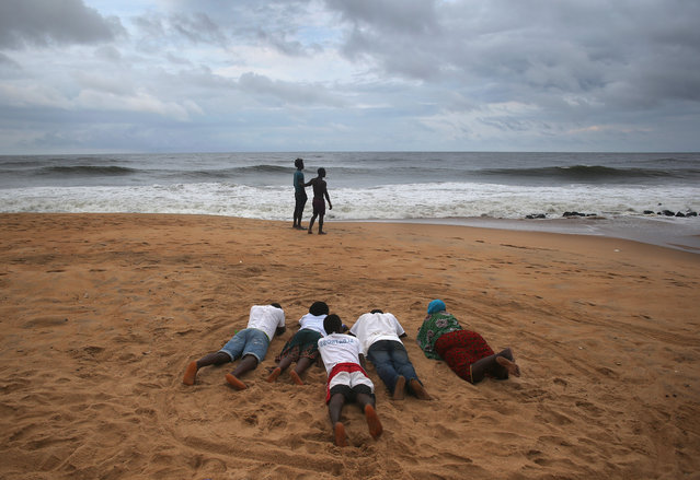 Members of the Church of Aladura pray on the beach on August 20, 2014 in Monrovia, Liberia. They said they were praying for God to rescue Liberia from its current crisis. The Ebola virus has killed more than 1,200 people in four African nations, with more in Liberia than any other country. (Photo by John Moore/Getty Images)