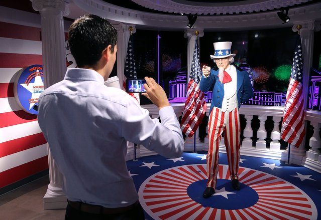 A guest takes a photo of a wax replica of Uncle Sam at a brand new interactive experience where Independence Day is celebrated every day at Madame Tussauds on July 18, 2016 in Washington, DC. (Photo by Paul Morigi/Getty Images for Madame Tussauds)