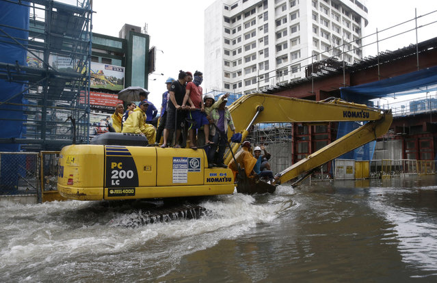 Filipino workers ride on a backhoe as they cross a flooded street in Manila, Philippines on Tuesday, September 12, 2017. (Photo by Aaron Favila/AP Photo)