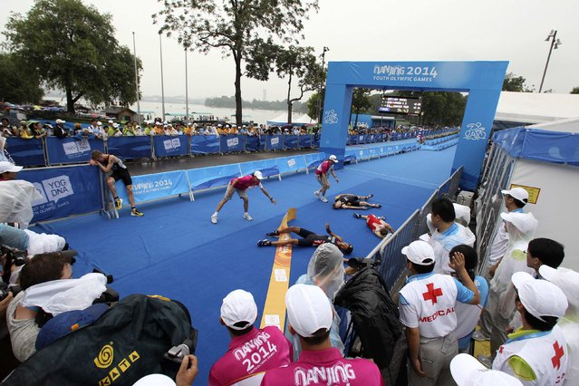 Athletes react after finishing the men's triathlon during the 2014 Nanjing Youth Olympic Games in Nanjing, Jiangsu province, August 18, 2014. (Photo by Aly Song/Reuters)