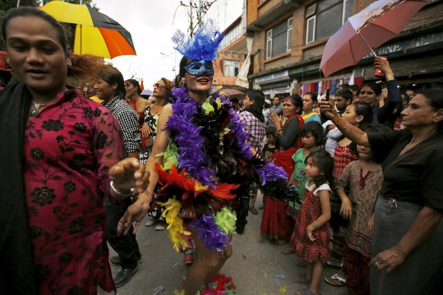 A reveller (C) dances while taking part in a LGBT (lesbian, gay, bisexual and transgender) pride parade to mark the Gaijatra Festival, also known as the festival of cows, in Kathmandu, Nepal August 30, 2015. (Photo by Navesh Chitrakar/Reuters)