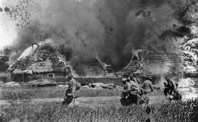 Austrian Infantry passing through a burnt-out village, 1914.