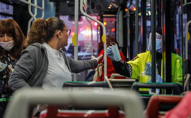A local police delivers a mask to a woman at a bus on the first working day in Valencia after Easter holidays during the coronavirus (COVID-19) crisis on April 14, 2020 in Madrid, Spain. The Spanish government has started to ease the lockdown to revive the country's economy. (Photo by Rober Solsona/Europa Press via Getty Images)