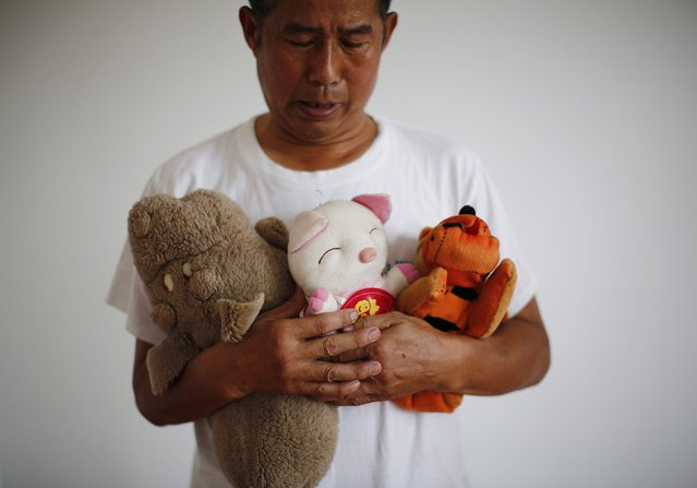 Zhang Yongli, whose daughter Zhang Qi was onboard Malaysian Airlines Flight MH370 which disappeared on March 8, 2014 looks at his daughter's plush toys as he poses for a picture, during an interview with Reuters in Beijing July 22, 2014. Zhang said this incident is disrupting the lives of he and his wife now. His wife sometimes roams several kilometers far from home because she cannot stand staying in their home from which her daughter is now absent. (Photo by Kim Kyung-Hoon/Reuters)