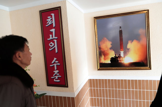 "In this November 26, 2019, photo, a man looks at a photo of the launch of a missile hanging on the wall of a factory workers' dormitory in Pyongyang, North Korea. Fears rise that North Korea's year-end deadline to the U.S. to offer some new initiative to the nuclear-standoff means that nearly two years of head-spinning diplomatic engagement might be in danger of falling apart. Sign in Korean reads; ""Highest level"". (Photo by Dita Alangkara/AP Photo)"